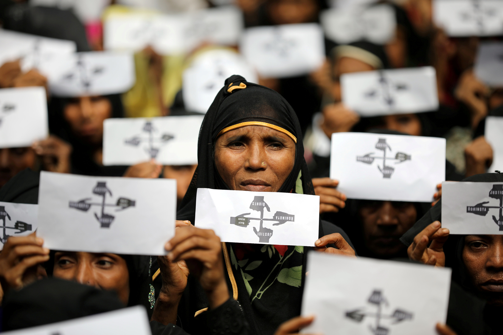 Rohingya refugee women hold placards as they take part in a protest at the Kutupalong refugee camp to mark the one-year anniversary of their exodus in Cox's Bazar, Bangladesh